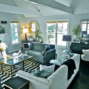 Esempio di un grande soggiorno chic aperto con pareti blu, parquet scuro, camino classico, cornice del camino piastrellata e TV a parete