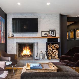 Ejemplo de sala de estar cerrada, clásica renovada, de tamaño medio, con paredes negras, suelo de madera en tonos medios, todas las chimeneas, marco de chimenea de baldosas y/o azulejos, televisor colgado en la pared y suelo marrón