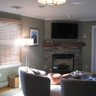 ニューヨークの中くらいのトランジショナルスタイルのおしゃれなファミリールーム (コーナー設置型暖炉、石材の暖炉まわり、壁掛け型テレビ、グレーの壁) の写真