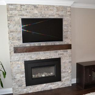 Foto de sala de estar con biblioteca cerrada, tradicional renovada, pequeña, con paredes beige, suelo de madera oscura, chimenea tradicional, marco de chimenea de piedra y televisor colgado en la pared
