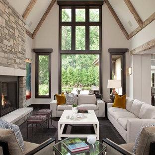 Modelo de sala de estar abierta, tradicional renovada, grande, con paredes blancas, chimenea tradicional, marco de chimenea de piedra, moqueta, suelo gris y pared multimedia