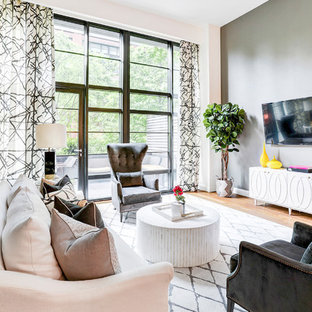Inspiration for a transitional medium tone wood floor family room remodel in New York with gray walls and a wall-mounted tv