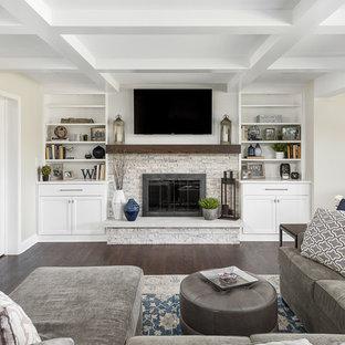 Diseño de sala de estar abierta, clásica renovada, grande, con paredes beige, suelo de madera oscura, todas las chimeneas, televisor colgado en la pared, marco de chimenea de piedra y suelo marrón