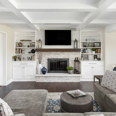Family room - large transitional open concept dark wood floor and brown floor family room idea in Chicago with beige walls, a standard fireplace, a wall-mounted tv and a stone fireplace