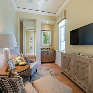 Small transitional enclosed medium tone wood floor and brown floor family room photo in Miami with beige walls, a wall-mounted tv and no fireplace
