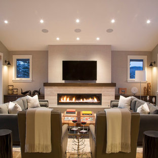 Example of a huge mountain style enclosed medium tone wood floor family room design in Denver with beige walls, a ribbon fireplace, a stone fireplace and a wall-mounted tv