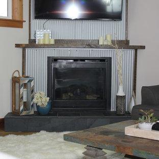 Cette photo montre une salle de séjour industrielle de taille moyenne et ouverte avec un mur blanc, un sol en bois foncé, une cheminée d'angle, un manteau de cheminée en métal, un téléviseur fixé au mur et un sol marron.