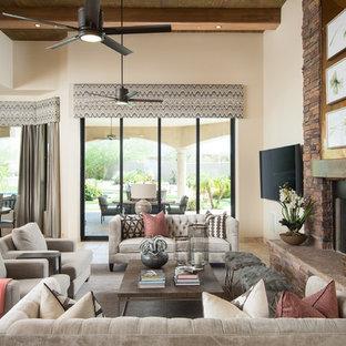Foto di un grande soggiorno chic aperto con pareti beige, pavimento in travertino, camino classico, cornice del camino in pietra, TV a parete e pavimento beige