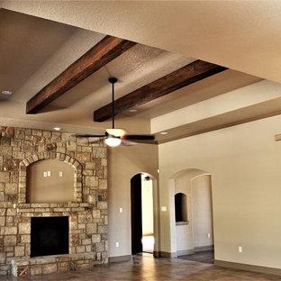 他の地域の大きいトラディショナルスタイルのおしゃれなファミリールーム (ベージュの壁、磁器タイルの床、標準型暖炉、石材の暖炉まわり、壁掛け型テレビ、茶色い床) の写真