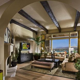 Ejemplo de sala de estar contemporánea, de tamaño medio, con paredes beige, chimenea de esquina, suelo de madera oscura, marco de chimenea de yeso, televisor colgado en la pared y suelo marrón