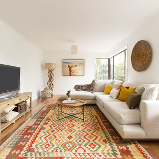 Design ideas for a mid-sized tropical family room in Sydney with white walls, medium hardwood floors, a freestanding tv and beige floor.