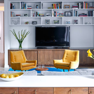Example of a trendy medium tone wood floor and brown floor family room design in New York with white walls and a wall-mounted tv