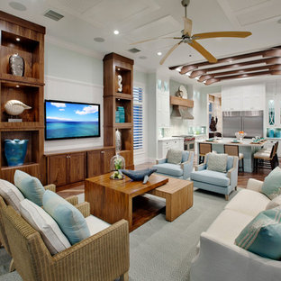 Large island style open concept medium tone wood floor family room photo in Miami with blue walls and a wall-mounted tv