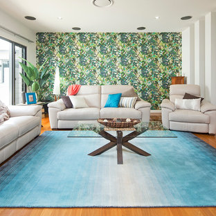 Photo of a large tropical open concept family room in Gold Coast - Tweed with medium hardwood floors and green walls.