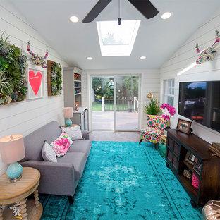 Imagen de sala de estar con barra de bar cerrada, bohemia, pequeña, con paredes blancas, suelo de ladrillo, televisor colgado en la pared y suelo marrón