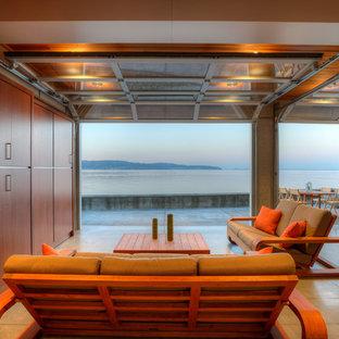 Foto de sala de estar abierta, actual, pequeña, con paredes beige, suelo de cemento, pared multimedia y suelo beige