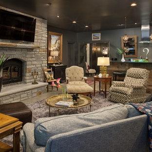 Foto de sala de estar con barra de bar cerrada, rural, con paredes negras, estufa de leña, marco de chimenea de piedra, televisor colgado en la pared y suelo gris