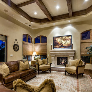 Family room - mediterranean dark wood floor family room idea in San Francisco with beige walls, a standard fireplace and a stone fireplace