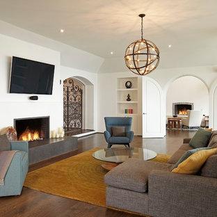 Imagen de sala de estar abierta, mediterránea, con paredes blancas, suelo de madera oscura, chimenea tradicional y televisor colgado en la pared