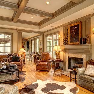 Imagen de sala de estar tradicional, sin televisor, con paredes beige, suelo de madera en tonos medios y chimenea tradicional