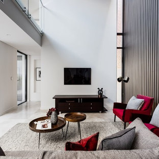 Contemporary open concept family room in Perth with white walls, a wall-mounted tv and grey floor.