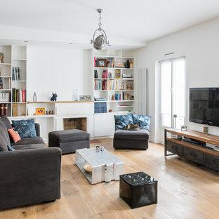 Cette photo montre une salle de séjour avec une bibliothèque ou un coin lecture industrielle de taille moyenne et ouverte avec un mur blanc, un sol en bois brun, une cheminée standard, un téléviseur fixé au mur et un manteau de cheminée en béton.