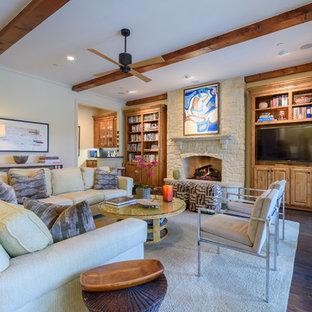 ダラスの大きいトラディショナルスタイルのおしゃれなファミリールーム (ホームバー、ベージュの壁、濃色無垢フローリング、標準型暖炉、石材の暖炉まわり、据え置き型テレビ、茶色い床) の写真