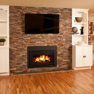 Imagen de sala de estar cerrada, actual, pequeña, con paredes beige, suelo de madera clara, chimenea tradicional, marco de chimenea de piedra y televisor colgado en la pared