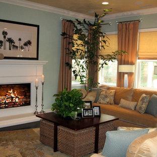 ロサンゼルスの中サイズのトロピカルスタイルのおしゃれなファミリールーム (濃色無垢フローリング、標準型暖炉、木材の暖炉まわり、青い壁) の写真