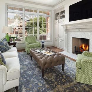 Modelo de sala de estar clásica, grande, con paredes blancas, suelo de madera oscura, chimenea tradicional, marco de chimenea de baldosas y/o azulejos, televisor colgado en la pared y suelo marrón