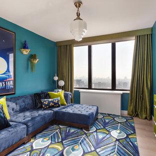 Diseño de sala de estar contemporánea, sin chimenea, con paredes azules y suelo de madera clara