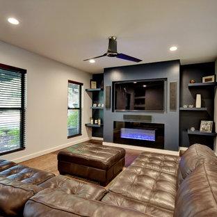 オースティンの中サイズのコンテンポラリースタイルのおしゃれな独立型ファミリールーム (グレーの壁、濃色無垢フローリング、横長型暖炉、タイルの暖炉まわり、埋込式メディアウォール) の写真
