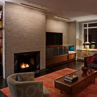 ニューヨークの大きいコンテンポラリースタイルのおしゃれなファミリールーム (ベージュの壁、濃色無垢フローリング、標準型暖炉、据え置き型テレビ、石材の暖炉まわり、茶色い床) の写真