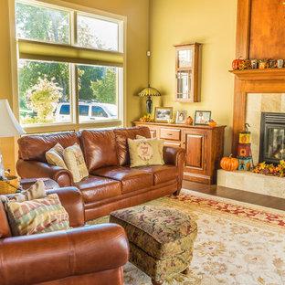 他の地域の大きいおしゃれなファミリールーム (ベージュの壁、標準型暖炉、石材の暖炉まわり、無垢フローリング、茶色い床) の写真