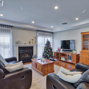 Photo of a mid-sized traditional enclosed family room in Other with grey walls, medium hardwood floors, a standard fireplace, a metal fireplace surround, a wall-mounted tv and brown floor.