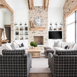 Ejemplo de sala de estar costera, grande, con paredes blancas, suelo de madera en tonos medios, chimenea tradicional, marco de chimenea de piedra y pared multimedia