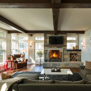 ミネアポリスの中サイズのラスティックスタイルのおしゃれなファミリールーム (無垢フローリング、標準型暖炉、石材の暖炉まわり、埋込式メディアウォール、グレーの壁、茶色い床) の写真