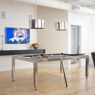 Cette photo montre une salle de séjour industrielle ouverte avec salle de jeu, un mur blanc, un sol en bois clair et un téléviseur fixé au mur.