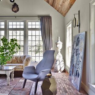 Modelo de sala de estar cerrada, campestre, grande, sin chimenea, con paredes beige, suelo de ladrillo y televisor colgado en la pared