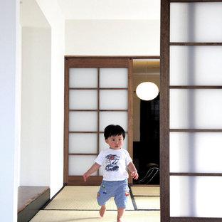 Exemple d'une salle de séjour tendance avec un mur blanc et un sol de tatami.
