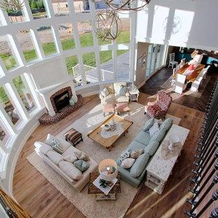 Modelo de sala de estar abierta, de estilo de casa de campo, extra grande, con paredes grises, suelo de madera clara, chimenea tradicional, marco de chimenea de ladrillo y televisor independiente