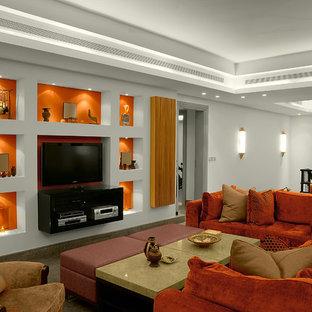Réalisation d'une salle de séjour mansardée ou avec mezzanine design avec un mur orange.