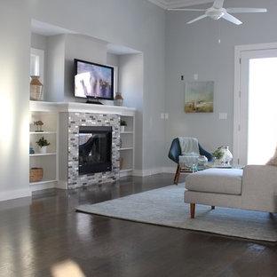 ボストンの広いビーチスタイルのおしゃれなオープンリビング (青い壁、無垢フローリング、タイルの暖炉まわり、据え置き型テレビ、茶色い床) の写真