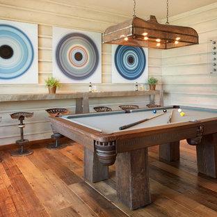Modelo de sala de juegos en casa rústica, sin chimenea, con suelo de madera en tonos medios