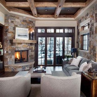 Ispirazione per un soggiorno rustico con pareti beige, camino ad angolo, cornice del camino in pietra e TV a parete