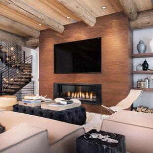 Modelo de sala de estar abierta, rural, de tamaño medio, con chimenea lineal, televisor colgado en la pared y paredes blancas