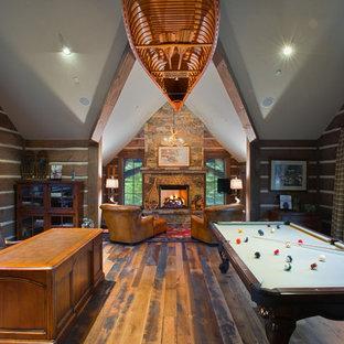 Imagen de sala de juegos en casa rústica, de tamaño medio, con paredes marrones, suelo de madera oscura, chimenea tradicional, marco de chimenea de piedra y televisor colgado en la pared