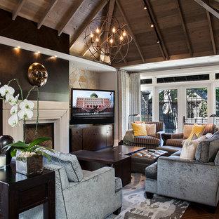 Aménagement d'une salle de séjour classique de taille moyenne et fermée avec un mur gris, un sol en bois brun, une cheminée standard, un manteau de cheminée en plâtre, télé d'angle et un sol marron.