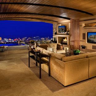 ラスベガスの大きいコンテンポラリースタイルのおしゃれなファミリールーム (ベージュの壁、標準型暖炉、壁掛け型テレビ、セラミックタイルの床、コンクリートの暖炉まわり) の写真
