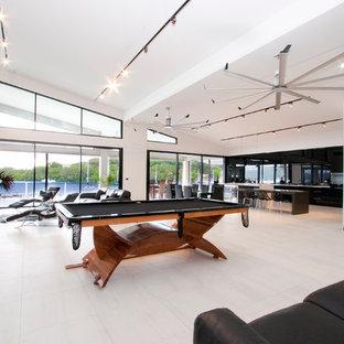 Cette image montre une salle de séjour design ouverte avec salle de jeu, un mur blanc et un sol blanc.
